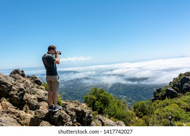 Mt Tamalpais State Park, CA, USA / June 1, 2019: San Francisco bay area visible in the background. A white Caucasian man taking a picture of the view wearing grey shirt and shorts.