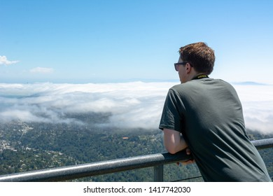 Mt Tamalpais State Park, CA, USA / June 1, 2019: San Francisco bay area visible in the background. A white Caucasian man looking at the view wearing grey shirt and sunglasses.