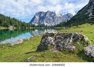 Mt. Zugspitze (highest mountain of Germany) with mountain lake in foreground.