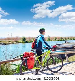 MTB Biker Bicycle touring on the river with pannier racks and saddlebag