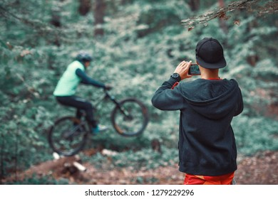 MTB teacher helping rider learn to ride bicycle. Teaching a rider to ride a bike on a trail.  Two friends have fun in nature and representing concept of fitness on mtb bike