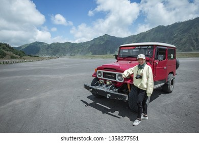 Mt.Bromo, Pasuruan, East Java, Indonesia - April 2018 : Lady with 4wd car on Adventure driving Off-road Jeep 4WD into Beautiful active Volcano with smoke Mount Bromo