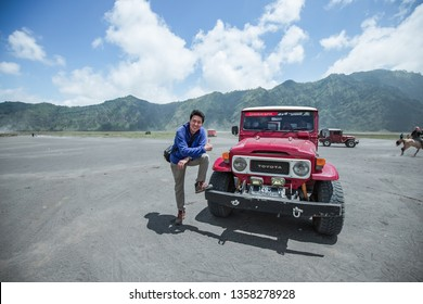 Mt.Bromo, Pasuruan, East Java, Indonesia - April 2018 : Man with 4wd car on Adventure driving Off-road Jeep 4WD into Beautiful active Volcano with smoke Mount Bromo
