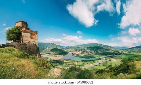 Mtskheta, Georgia. The Ancient Georgian Orthodox Church Of Holly Cross, Jvari Monastery With Remains Of Stone Wall, World Heritage. Scenic Blue Cloudy Sky Background. Panorama