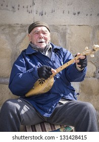 MTSKHETA, GEORGIA - MARCH 10: Georgian man plays a traditional Georgian instrument called fanduri and sings for money in front of the church in Mtskheta on March 10, 2013.