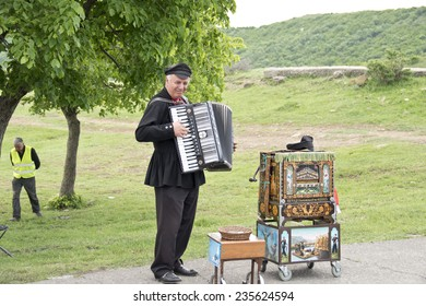 MTSKHETA, GEORGIA - MAY 9: Unidentified street musician plays the accordion near the ancient Djvari Church in Mtsketa, Georgia on May 9, 2014. He is genius and can play the barrel organ (right) also.