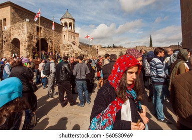 MTSKHETA, GEORGIA - OCT 14: Faces of people coming to the historical christian Svetitskhoveli Cathedral, built in 4th century on October 14, 2016. UNESCO World Heritage Site.