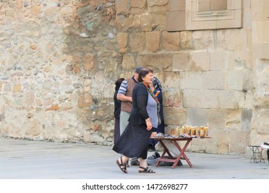 Mtskheta, Tbilisi, Georgia. July 2019. Some  local people tries to sell souvenirs and traditional cand, to the tourists, at the entrance of the Svetiskhoveli unesco site cathedral.