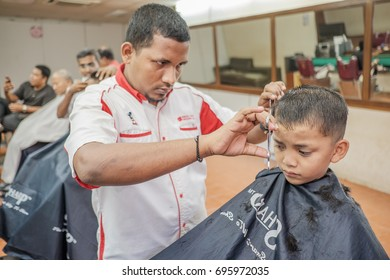 Muadzam Shah, Malaysia - August 14th, 2017 : Little boy getting warber while sitting haircut on chair at barbershop.