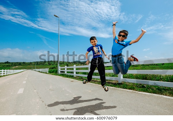 Muadzam Shah, Malaysia - December 18, 2016 : Happy boys play on the road having great holidays time on school holiday at First Dairy Farm, Muadzam Shah   . Lifestyle, vacation, happiness, joy concept
