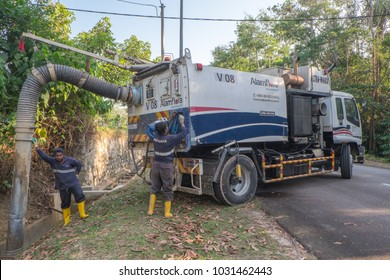 """Muadzam Shah, Malaysia- February 21st, 2018 : Municipal worker """"Alam Flora"""" uses water spray jets and suction machines to clean rubbish and sand in the drain and put into a garbage truck."""