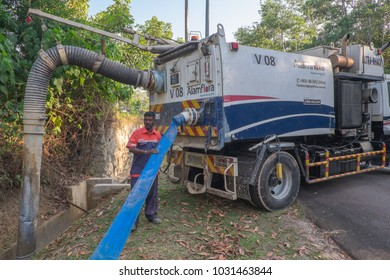 """Muadzam Shah, Malaysia - February  21st, 2018 :  Municipal worker """"Alam Flora"""" uses water spray jets and suction machines to clean rubbish and sand in the drain and put into a garbage truck."""
