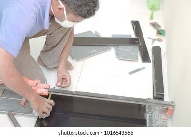 Muadzam Shah, Malaysia - February 3rd, 2018 : Man mark the tile to be cut into layers of ceramic floor tiles