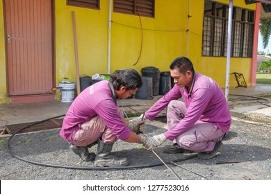 Muadzam Shah, Malaysia - January 3rd, 2019 : The worker clears the clogged sewer drain using drain clog remover  to remove the dirt attached to the channel.