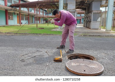 Muadzam Shah, Malaysia - January 3rd, 2019 : The worker clears the clogged sewer drain using drain clog remover