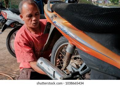 Muadzam Shah, Malaysia - March 2nd, 2018 :Mechanic fixing motocycle change tyre.