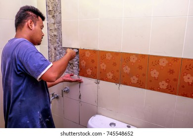 Muadzam Shah, Malaysia - October 31st, 2017 : Repairs of the bathroom wall tiling.  Tiler laying wall ceramic tiles on adhesive using tiling tools.
