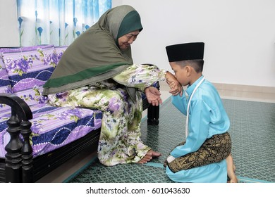Muadzam Shah-July 17, 2015 : Grandson and grandmother asking forgiveness during Eidul Fitri celebration at Batu Pahat, Malaysia.