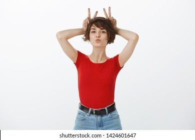 Muah. Temtping alluring good-looking silly girl short dark haircut folding lips kiss mwah show bunny rabbit ears behind head acting playful flirty look cute camera standing white background