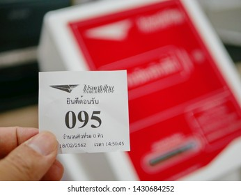 Muang, Chaing Mai / Thailand - February 18 2019: A hand holding a waiting queue ticket at a Thai post office with a defocus of a queue-ticket dispenser in the background at Muang district, Chiang Mai