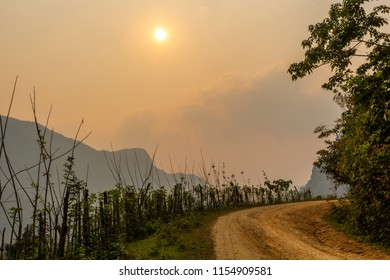 Muang Ngoi, Laos - April 10, 2018: Paved road in the countryside of northern Laos surrounded by foggy mountains. Credit: Dino Geromella/Shutterstock