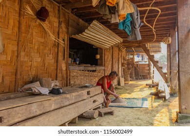 Muang Ngoi, Laos - April 10, 2018: Local man making a hand made typical asian hat in front of his house in a remote village of northern Laos. Credit: Dino Geromella/Shutterstock