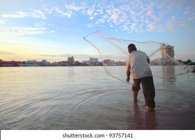 MUAR,MALAYSIA - JAN 1:A fisherman casts his net from the side of Muar estuary river during sunrise on Jan 1 ,2011.Fishing  is still the major economy of some fishing villages in this suburban district