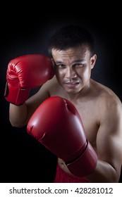 muay thai boxer man trainings. studio shot on black background
