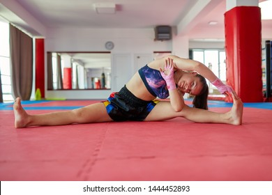 Muay thai female fighter stretching and warming