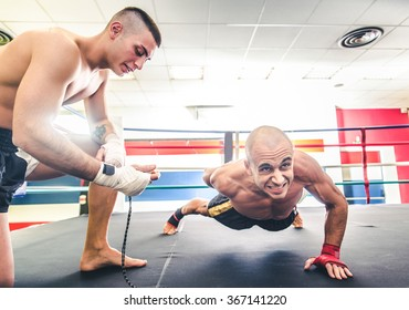 Muay thai fighter doing push ups  - Coach training his athlete for a boxe match - Sportive men working out in a martial arts gym