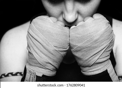 Muay Thai fighter girl preparing for battle. Closeup black and white portrait against black background.