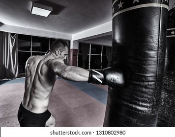 Muay thai fighter hitting the heavy bag in the gym