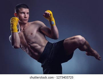 Muay thai or kickboxer executing a powerful kick against black background