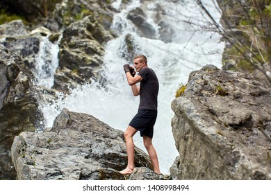 A muay thai or kickboxer training with shadow boxing by a strong waterfall