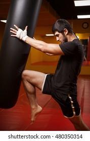 Muay thai training. man in gym kick bag.