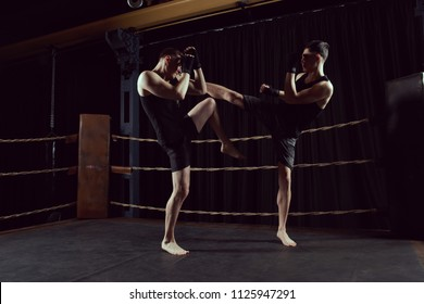 Muay Thai. Two man fightning, boxing or kickboxing on ring. Sport concept. Dark gym.