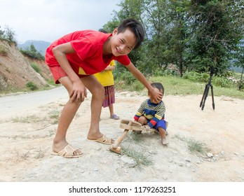 MUCANGCHAI, VIETNAM, Septmber 24, 2016: H'mong ethnic minority boy in Mucangchai, Vietnam plays with a custom built wooden car. H'mong is the 8th largest ethnic group in Vietnam.