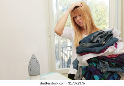 too much domestic work - too many clothes to iron and young exhausted and annoyed housewife at home - focus on pile of clothes to iron