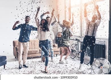 So much fun! Full length of happy young people dancing while spending time at home with confetti flying everywhere