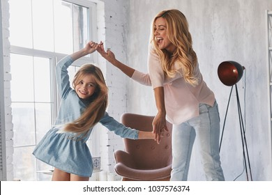 So much fun! Full length of mother and daughter holding hands and smiling while dancing in bedroom