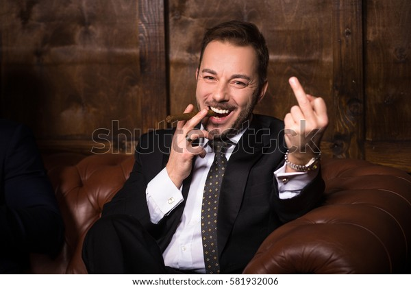 Much money is ability to send all in ass. Happy handsome rich man smoking cigar and giving fuck off while sitting on sofa in men's club. Luxury concept.
