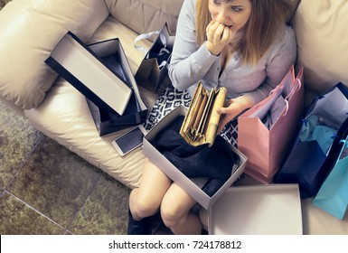 too much shopping young woman after over-spending looking at empty wallet.  concept of luxury addiction and consumerism