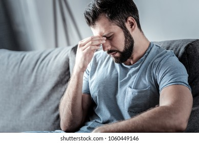 Too much stress. Sad unhappy bearded man sitting on the sofa and holding his bridge of nose while feeling tired