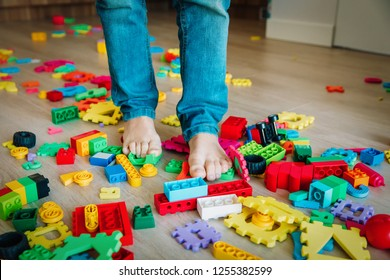 too much toys at home- little boy steps on toys trying to go through