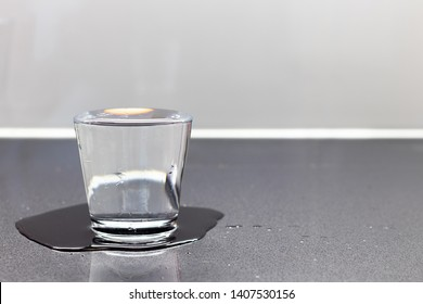 Too much water in the glass, spilled over the edge to the table