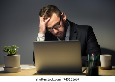 Too much work concept. Troubled man in glasses reading about recent problem on laptop, deep in thoughts about best course of actions. Hand supports head, covering forehead, face palm gesture .
