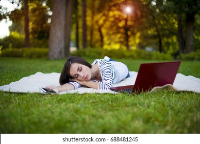 Too much work. Young business woman asleep while working behind a laptop in the park