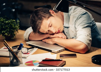 Too much work. Young man sleeping at his working place while leaning his head on the laptop