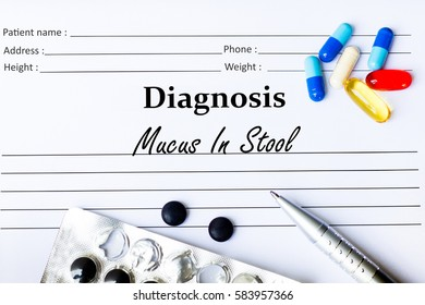 Mucus In Stool -  Diagnosis written on a piece of white paper with medication and Pills
