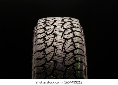 mud all terrain tires for SUVs on a black background close-up, front view of the wheel, the tread can be clearly seen